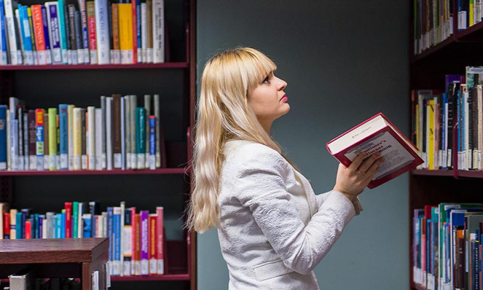 Student working in library shelving books